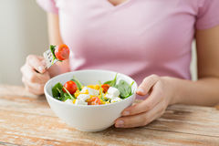 Close up of young woman eating salad at home Stock Photo