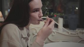 Close up young woman eating small piece of tasty cake in the cafe. The girl enjoying her dessert in the modern. The hands of the young woman eating a small piece stock footage
