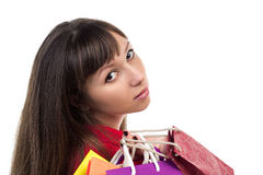 Close-up of young woman face with colourful shopping paper bags royalty free stock photos