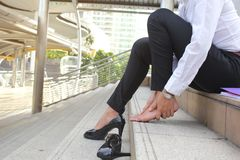 Close-up young woman feeling pain in her foot on stair, Have ankle pain, Health concept stock photography