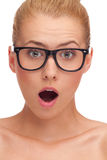Close-up of a young woman in glasses looking surprised. stock images