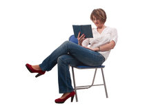 Close up of young woman with glasses sitting on chair and readin Stock Image
