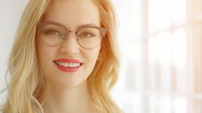 Close up of young woman in glasses with sunlight royalty free stock photography