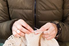 Young woman   knits. Close-up of a young woman in a green jacket and knits with natural woolen threads of a beige sweater Stock Images