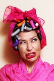 Close-up of a young woman with hair curlers making a grimace Royalty Free Stock Image