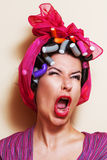 Close-up of a young woman with hair curlers making a grimace Stock Photos