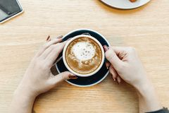 Close up of woman hands holding cup of coffee. Top view. stock photography