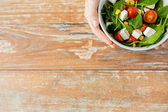 Close up of young woman hands with salad bowl. Healthy eating, dieting and people concept - close up of young woman hands with salad bowl on blank table at home Royalty Free Stock Image