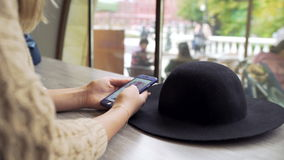 Close up of young woman hands typing message on phone in cafe. In Moscow, there is black hat on the table stock footage