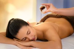 Therapist pouring hot chocolate massage oil on young woman royalty free stock photography