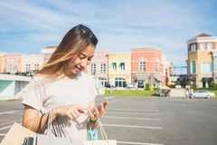 Close up of a young woman hold a shopping bags in her hand and chatting on her phone after shopping. Stock Images
