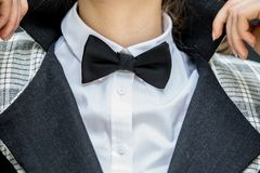 Close up of young Woman holding her collar in white shirt and bl. Ack and gray jacket and a black bow tie Royalty Free Stock Image