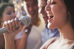 Close- up of young woman holding a microphone and singing at karaoke, friends singing in the background royalty free stock images