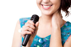 Close up young woman holding microphone. Smiling young female in sparkling blue dress, singing, holding microphone, close-up of mic, isolated on white background royalty free stock photography