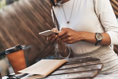 Getting good feedback from client. Close-up of young woman holding a smart phone while sitting in restaurant outdoors Stock Images