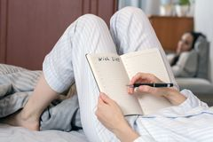 Close-up of a young woman in home pajamas lying in bed and making a wish list. concept of planning, goals, future,. Mode day Royalty Free Stock Photos