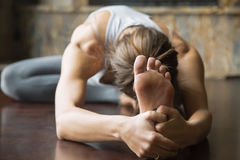 Close up young woman in Janu Sirsasana pose, home interior. Close up of young woman practicing yoga, sitting in Head to Knee Forward Bend exercise, Janu Stock Photo