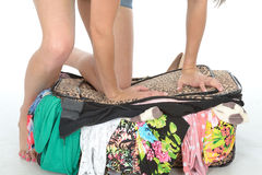 Close Up of Young Woman Kneeling on Suitcase Trying to Close it Royalty Free Stock Photos