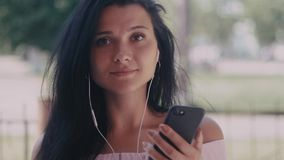 Close up shot of young woman listening music in the headphone while using smartphone in the city. Portrait shot. Close up of young woman listening music in the stock video