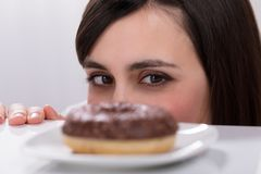 Young Woman Looking At Donut stock photography