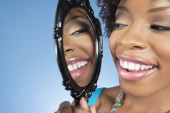 Close-up of a young woman looking at herself in mirror and smiling over colored background Royalty Free Stock Image