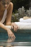 Close-up of a young woman lying at the poolside. Hand draped in the water Royalty Free Stock Image