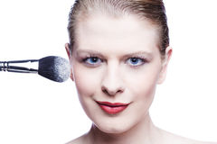 Close up of young woman with make up brush. Isolated on white Stock Images