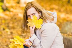 Close-up of young woman with maple autumn leaves. Close-up young woman with maple autumn leaves Stock Photo