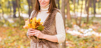 Close-up of young woman with maple autumn leaves. Close-up young woman with maple autumn leaves Royalty Free Stock Photography