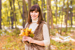 Close-up of young woman with maple autumn leaves. Close-up young woman with maple autumn leaves Royalty Free Stock Photo