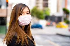 Close up of a young woman with protective mask feeling bad on the street in the city with air pollution, city background Stock Image