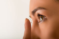 Close up of a young woman putting contact lens in her eye close up Royalty Free Stock Image