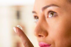 Close up of a young woman putting contact lens in her eye close up.  Stock Images