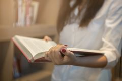 Close up young woman reading a book at a library. Royalty Free Stock Photos