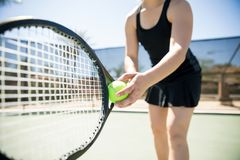 Tennis player serving ball. Close up of a young woman ready to hit a tennis ball, serving a ball during game Stock Photography