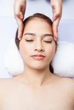 Close-up of young woman receiving facial massage at day spa Stock Images