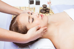 Close-up of young woman receiving facial massage at day spa Stock Photography