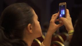 Close-up of young woman recording a video of business presentation in conference hall. Art. Business meeting stock video