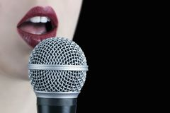 Close up of a young woman with red lips singing to the microphone isolated on black background stock photos