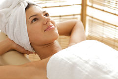 Close-up of young woman relaxing on massage table with hands behind head Stock Photography