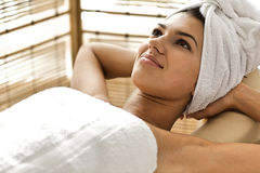 Close-up of young woman relaxing on massage table with hands behind head. Close-up of young women relaxing on massage table with hands behind head Stock Photo