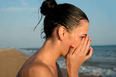 Close-up of a young woman  rubbing  irritated sens. Close-up of a young woman rubbing  irritated sensitive eyes on the beach, allergy reaction Stock Image