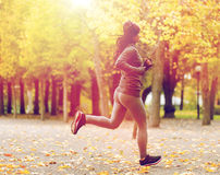 Close up of young woman running in autumn park. Fitness, sport, people, wear and healthy lifestyle concept - close up of young woman running in autumn park Royalty Free Stock Images