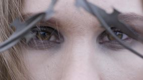 Close-up of a young woman`s eyes through barbed wire. Action. Beauty fashion concept.  stock video