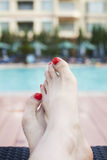 Close up of young woman's feet by the edge of the pool Royalty Free Stock Photo