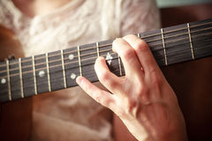 Close up on young woman's hand playing guitar Royalty Free Stock Photo