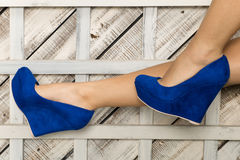 Close-up of young woman`s legs in high-heeled blue shoes. Studio shot on wooden background. Royalty Free Stock Photos