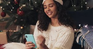 Close up of young woman in santas hat sitting under the cristmas tree at holiday decorated home background while. Chatting via her smartphone, typing message stock video footage