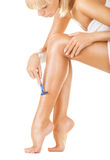 Shaving legs. Close-up of a young woman shaving legs isolated on white background Stock Image