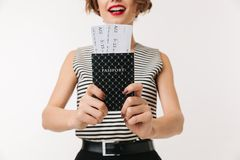 Close up of a young woman showing passport with tickets. Close up of a young woman showing passport with flying tickets isolated over white background Royalty Free Stock Image